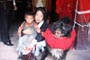 Tenkila Jamyangling and a small child take a picture with a Tibetan mastiff guard dog